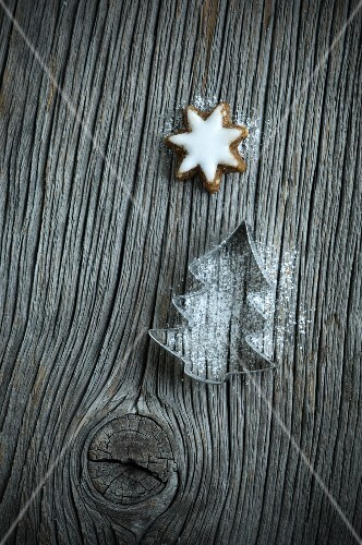 A Christmas tree-shaped cutter with icing sugar and cinnamon stars on a wooden board