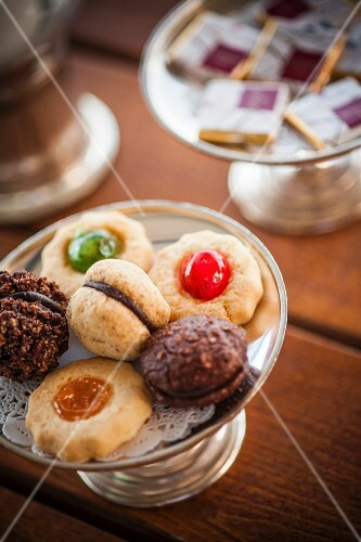 Various mini biscuits on a silver stand with a doily