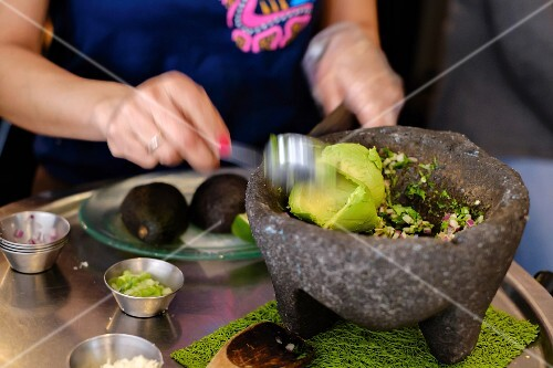 A woman making guacamole in a stone mortar