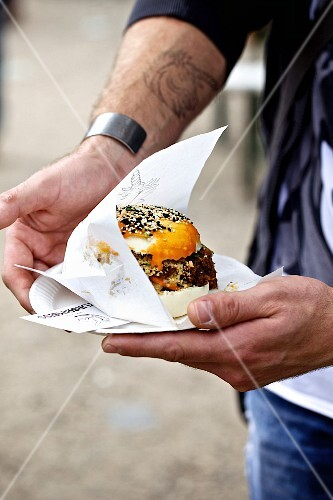 A person holding a Gua Bao burger with sesame seeds (oriental street food)