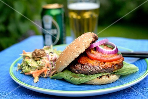 A hamburger and a beer on a table outside