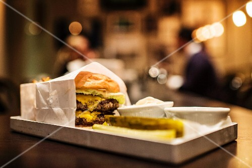 A hamburger, dips and gherkins on a tray on a counter