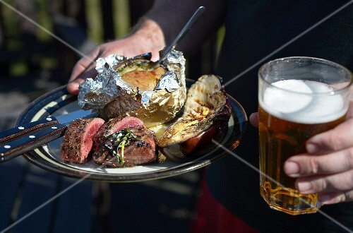 A person holding a plate of grilled lamb, baked potato and aubergine