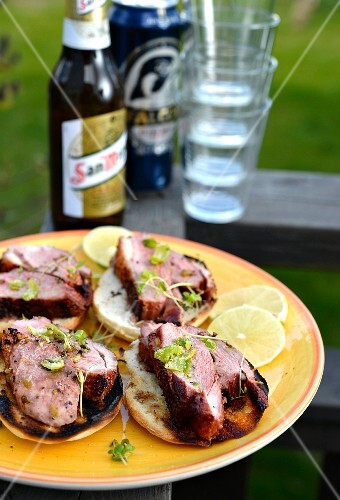 Duck breast on slices of toast with beer and glasses in the background