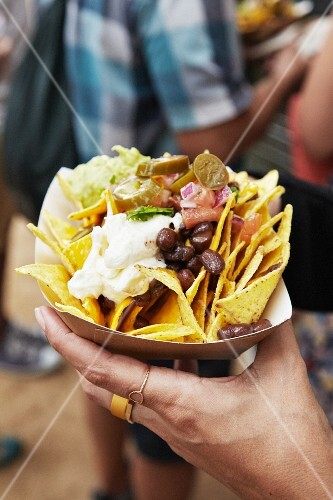 A hand holding a paper bowl of tortilla chips and beans at a market (Barcelona, Spain)