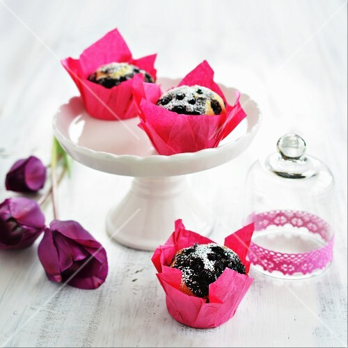 Blueberry muffins on a cake stand and next to a glass cloche