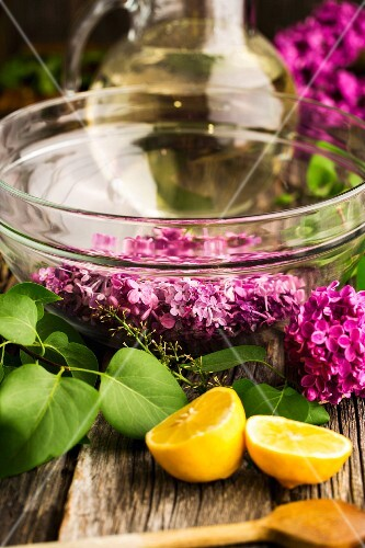 Lilac flower syrup being made: flowers in a glass bowl with sugar syrup in the background