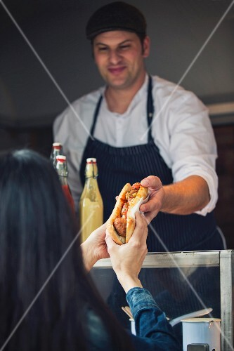 A seller at a fast food stall handing a woman a meatball sandwich