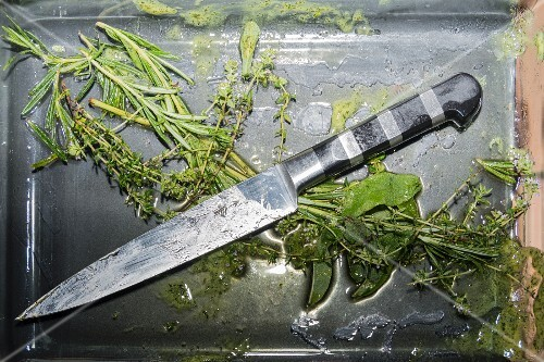 The remains of herbs and the meat knife on a used baking tray
