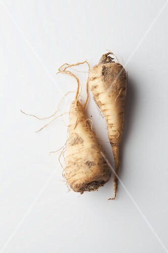 Two parsnips on a white surface