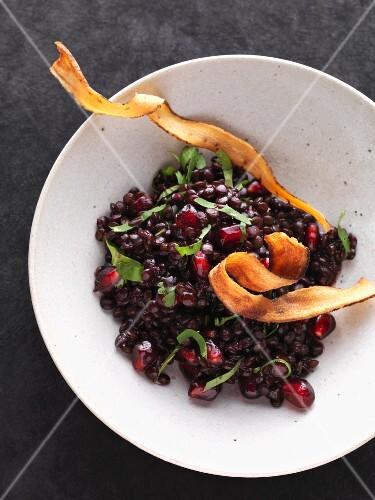 Beluga lentil salad with pomegranate seeds and black salsify crisps