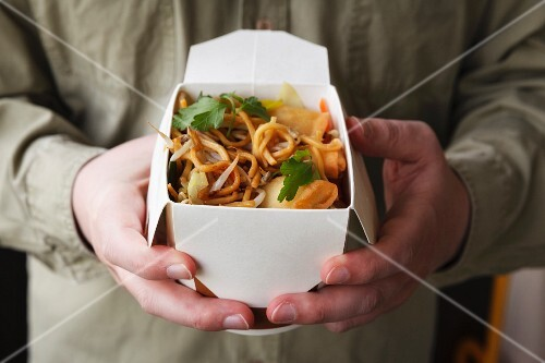 A man holding a box of fried noodles and spring rolls
