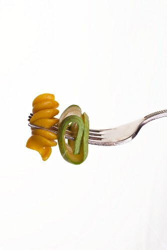 Wholemeal fusilli pasta and courgette on a fork