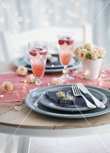 A place setting with chocolate pralines and strawberry champagne