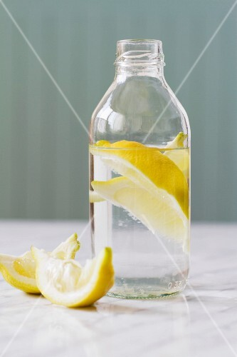 Water with lemon wedges in a glass bottle