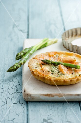 Asparagus and smoked salmon tartlets with asparagus spears on white chopping board