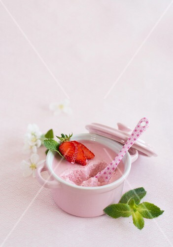 A bowl of strawberry mousse with a bite taken out