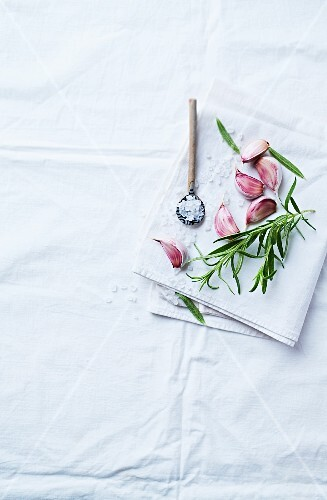 Garlic cloves, rosemary and sea salt on a linen cloth