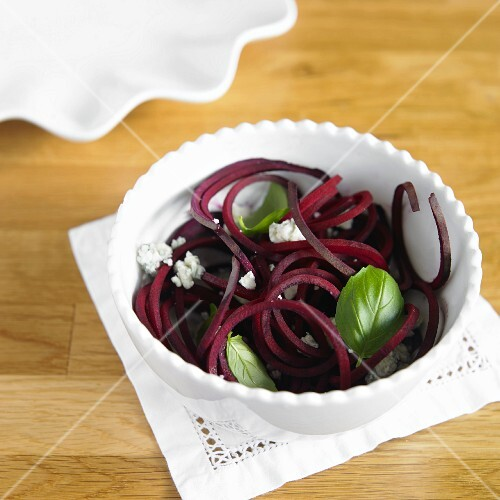 Vegetable spaghetti made from beetroot with Gorgonzola and basil in a white bowl