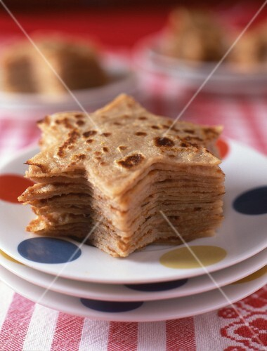A stack of star-shaped crepés on a spotted plate