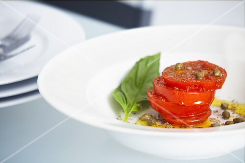 Sliced tomatoes with caper vinaigrette and a basil leaf