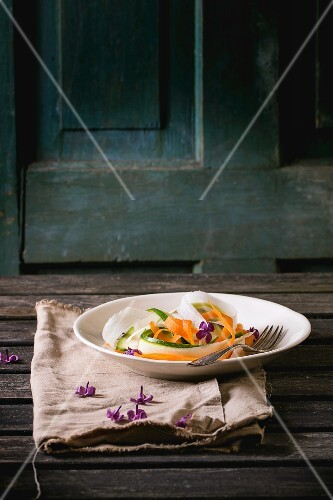 Grated vegetable tagliatelle made of carrots, radish and courgette on a plate with lilac flowers