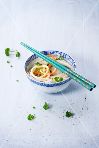 Vegetable noodles with parsley and sesame seeds in an oriental bowl with chopsticks