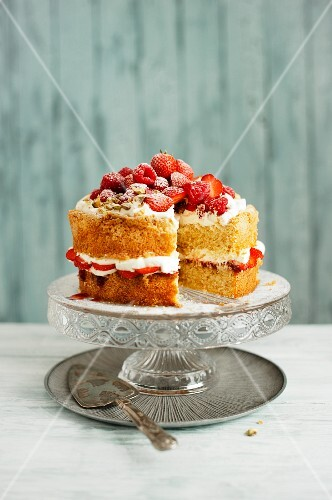 A Victoria sponge cake with cream, strawberries, raspberries and pistachios on a cake stand
