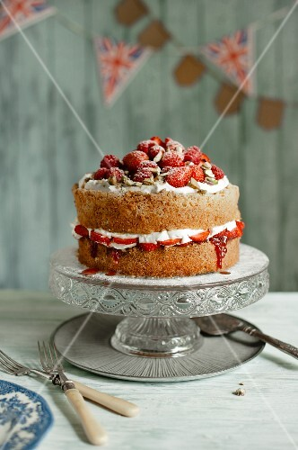 A whole Victoria sponge cake with cream, strawberries, raspberries and pistachios on a cake stand