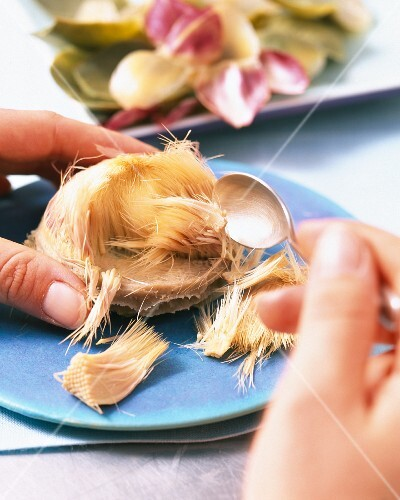 An artichoke heart being removed