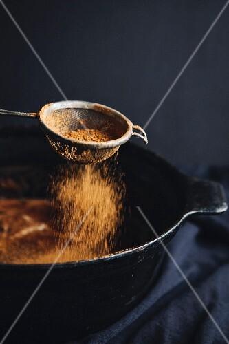 Ground cinnamon being sprinkled on pancakes
