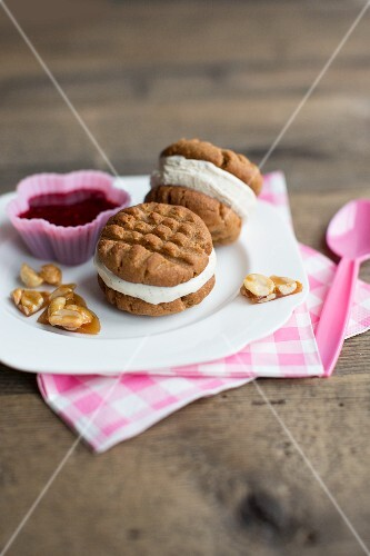Peanut butter ice cream sandwiches with red berry sauce and peanut brittle