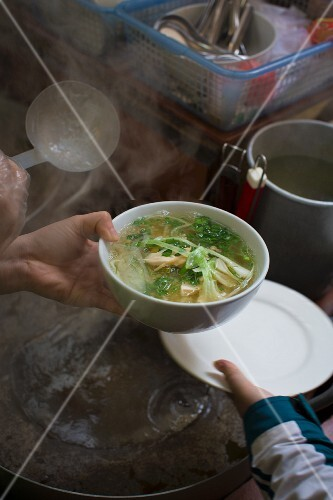A steaming bowl of Vietnamese Pho soup in a street kitchen