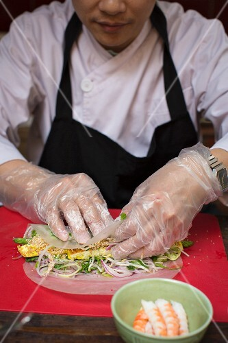 A chef preparing a Vietnamese spring roll with tofu
