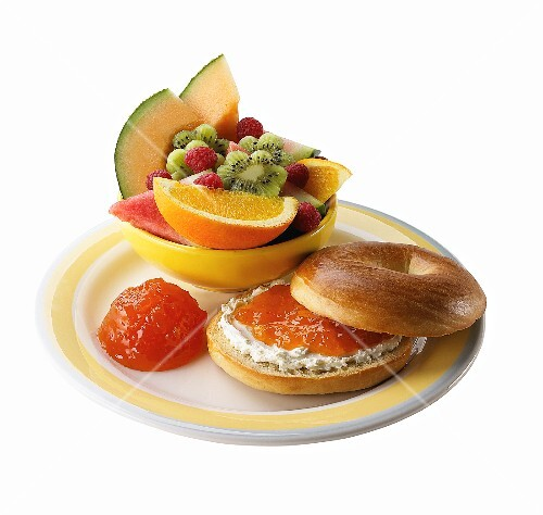 A bagel with cream cheese, peach jam and fruit