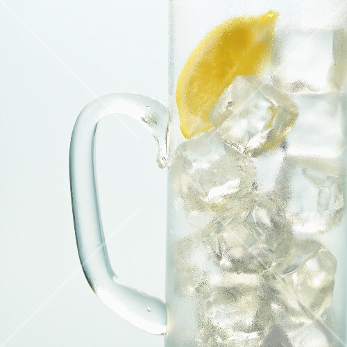 Ice cubes and lemons in a glass jug