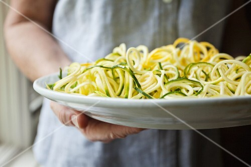 A person holding a plate of cooked courgette noodles