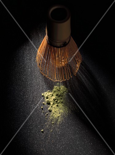Matcha tea powder and a bamboo whisk