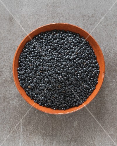Organic black Beluga lentils in a terracotta dish (seen from above)