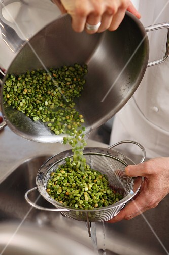 Cooked green lentils being drained