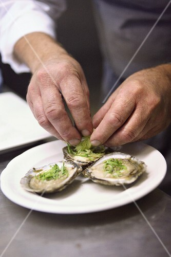 Oysters being garnished