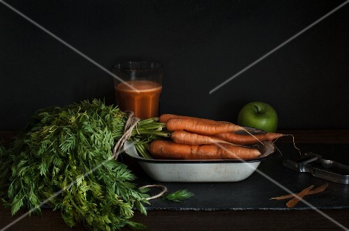 A bunch of carrots in an enamel bowl with carrot juice and an apple