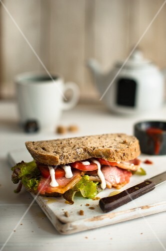 Bacon, lettuce and tomato sandwich with mayonnaise on a chopping board