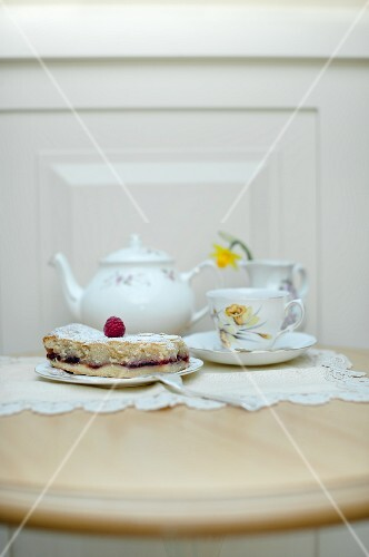 A slice of Bakewell tart (almond and raspberry jam tart, UK) with a vintage teapot and tea cup on a table