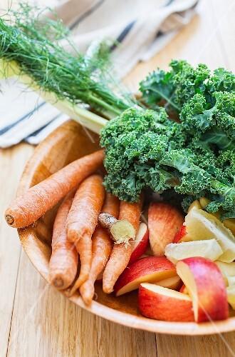 Carrots, ginger, kale, celery, apples and lemons in a wooden bowl