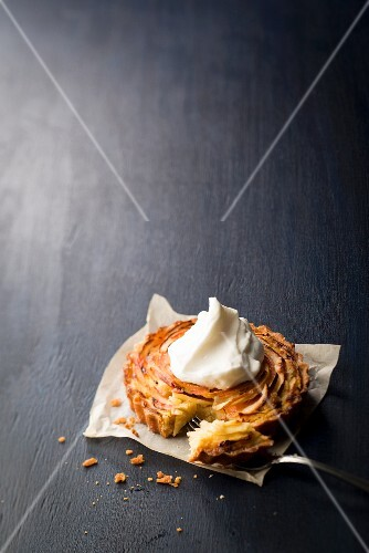 Apple tartlet with a dollop of cream and a bite taken out