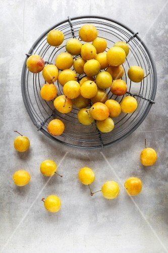 Yellow plums in a wire basket
