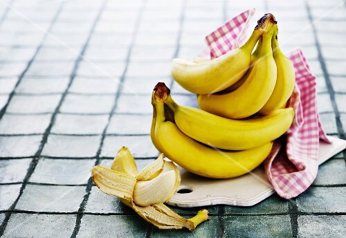 Bananas, whole and peeled, on a chopping board with a towel