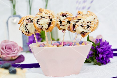 Mini blueberry pastries on sticks in a pink bowl