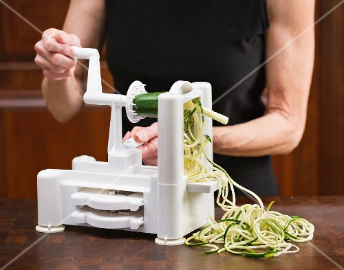 A woman preparing courgette noodles with a spiral cutter